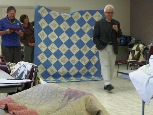 Gerald Roy explains a key point on a quilt